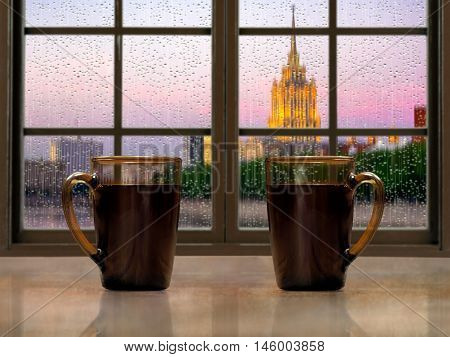 Two mugs with a hot drink - tea or coffee on the window sill of the window. During the early morning the city the rain. Concept - good morning alertness awakening together