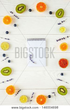 Colorful pattern made of fruits with laveder, blank open notebook aon white background
