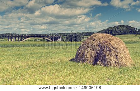 Lonely haystack and remains of old bridge in countryside by summer day