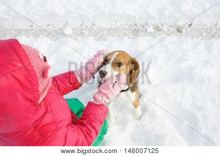 Little girl playing with her dog in a snowy landscape having winter fun. Active family lifestyle outdoor and natural childhood fun and carefree childhood concept.