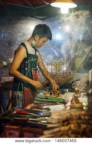 Young Woman Cooks Fish And Seafood