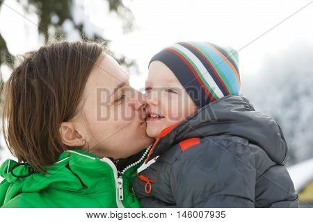Mother kissing her son in a snowy winter landscape bonding having fun smiling talking and enjoying family time. Mothers day family values parents love and happy childhood concept.