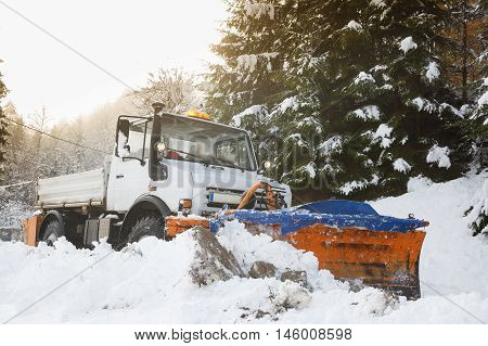 Snow plough making its way through the snowy country road in the morning clearing it of snow after blizzard. Professional winter services road conditions in winter concept.