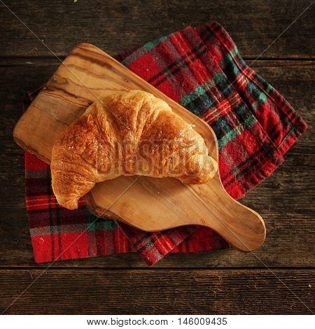 Fresh homemade croissant on a cutting board