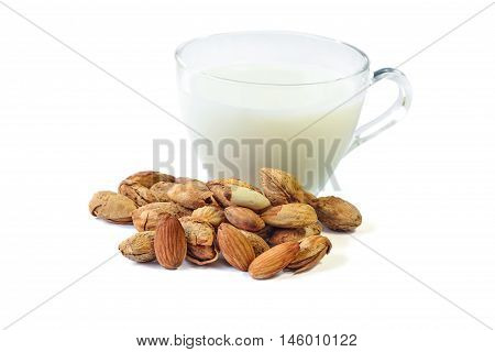 Roasted Almond nut in shell and a cup of almonds milk on white background