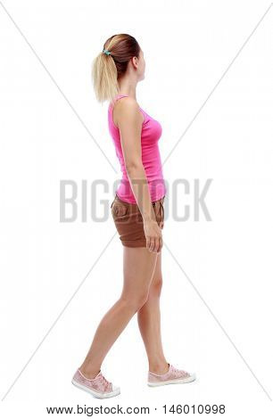 back view of walking woman. beautiful blonde girl in motion. Isolated over white background. Sport blond in brown shorts thoughtfully looks aside in passing.