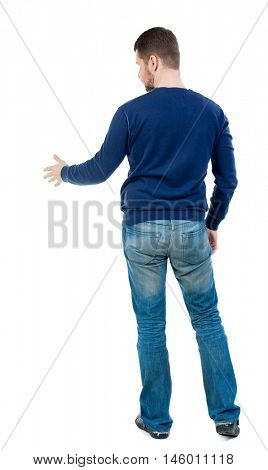 back view of businessman reaches out to shake hands. bearded man in blue pullover extends his hand in greeting.