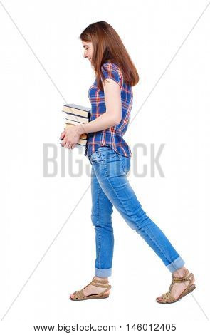 Girl comes with stack of books. side view. Girl in a plaid shirt goes to the sad side with textbooks.