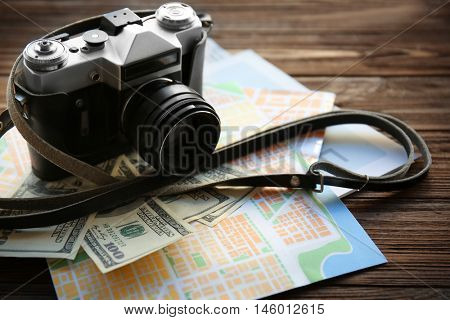 Vintage camera with map and cash on wooden table
