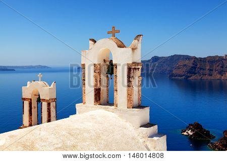 Church bells and crosses in Oia Santorini. Volcano and sea on background