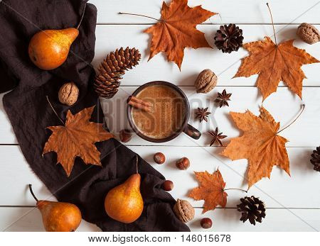 Autumn composition with hot pumpkin latte with cinnamon, scarf, nuts and leaves. Concept of cozy morning, comfort, relax, melancholy, fall weather, home. Vintage white table background. Rustic style.