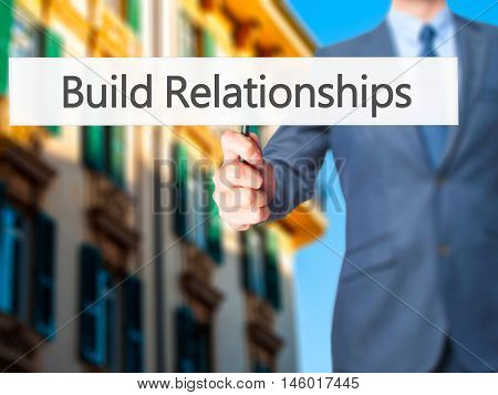 Build Relationships - Businessman Hand Holding Sign