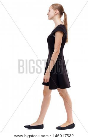 back view of walking woman. beautiful girl in motion. Isolated over white background. Blonde in a short black dress out of the frame.