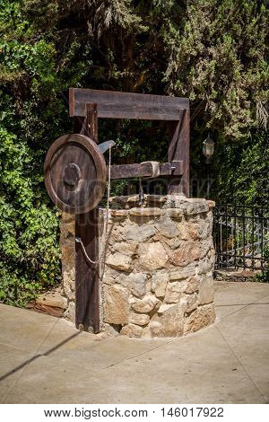 Ancient stone water well with hand wooden winch near the entrance to the archaeological park of Shiloh in Samaria, Israel