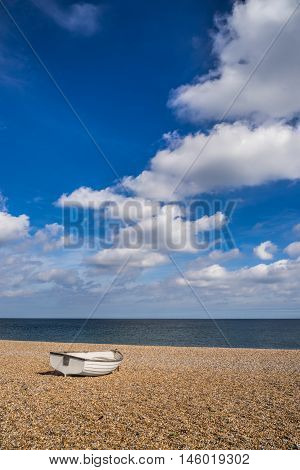 Single rowing boat ona shingle beach facing out to sea on a bright sunny summers day