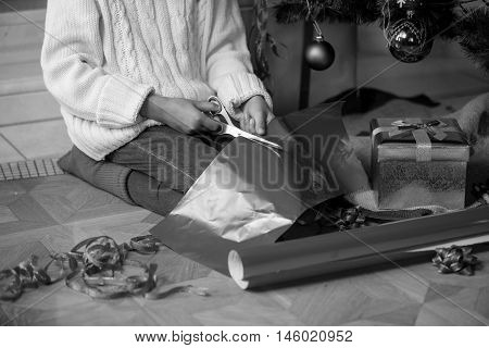 Black and white closeup image of cute girl cutting wrapping paper under Christmas tree at living room