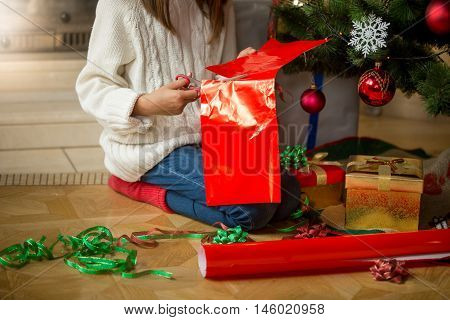 Closeup image of young girl wrapping presents under Christmas tree