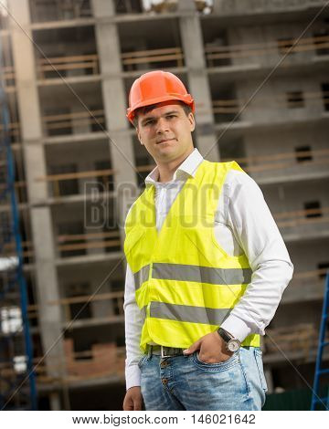 Portrait of young construction engineer standing at building site and looking at camera
