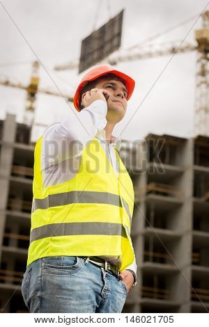 Toned portrait of young construction engineer talking by phone on construction site. Crane lifting heavy blocks on background