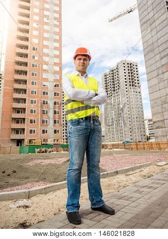 Portrait of smiling young architect standing at building place