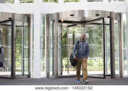 Middle aged black man entering the foyer of modern building