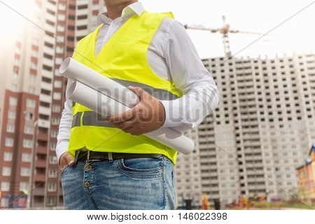 Closeup image of male foreman holding rolled blueprints