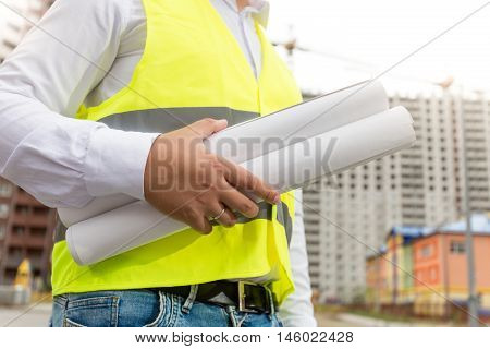 Closeup photo of engineer in safety vest holding rolled blueprints