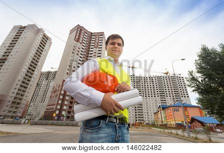 Portrait of young construction engineer in safety vest holding hardhat