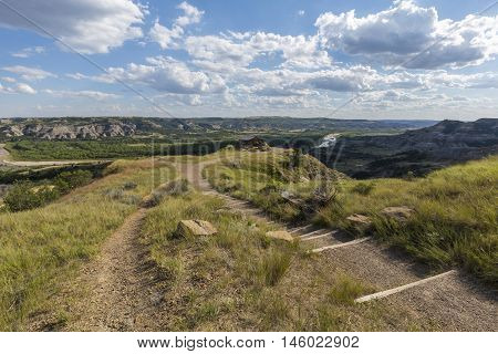 A trail leading to a scenic view of a badlands river valley.