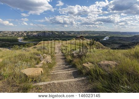 A trail leading to a scenic view of a badlands landscape.