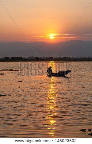 Fisherman silhouette at sunset in Inle Lake Myanmar. Vertical shot