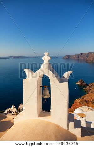 Church bell in Oia Santorini Greece. Sea and volcano on background. Vertical shot