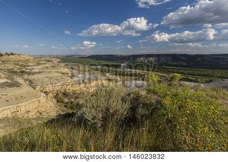 A wide scenic view of a badlands river valley.