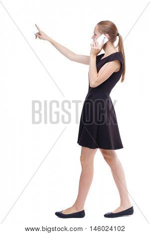 side view of walking woman. Rear view people collection. Isolated over white background. Blonde in a short black dress is divided gossip on the phone