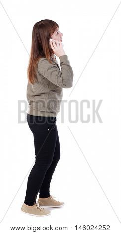 side view of a woman walking with a mobile phone. back view of girl in motion. A girl in a gray jacket talking on the white smartphone.