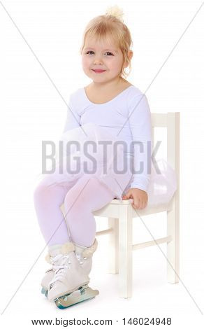 Cute little girl, a future figure skater, sits on a chair in a White sports dress and figure skates on two skids-Isolated on white background