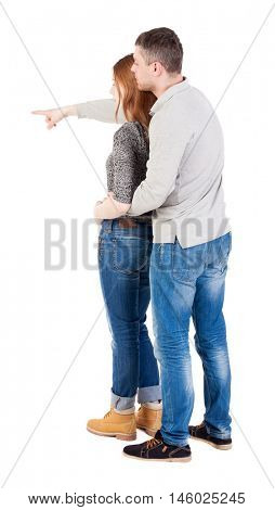 young couple pointing at wal Back view   Rear view people collection.    Isolated over white background. Man hugging his wife and shows his hand forward.