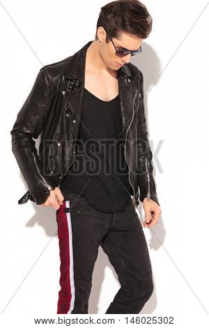 fashion man in leather jacket and sunglasses looking down on white background