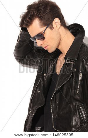 side view portrait of a sad fashion man in leather jacket looking down on white background