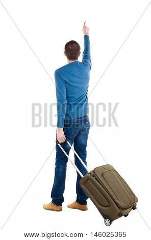 back view of  pointing man  with suitcase. brunette guy pointing .  backside view of person.  Rear view people collection. Isolated over white background. guy with a travel bag on wheels looking at