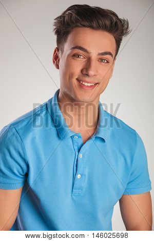positive young casual man in polo shirt laughing and looks to the camera