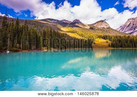 The smooth turquoise water in the wooded mountains. Charming mountain Emerald lake. Yoho National Park, Canada. Sunny day in autumn. The concept of eco-tourism