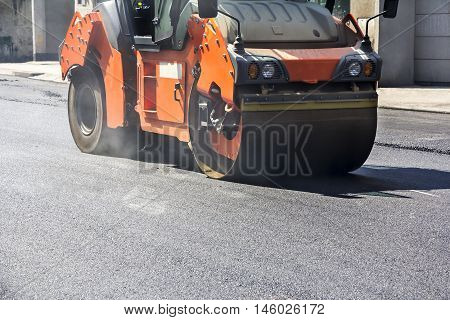 Roller compactor working on the new road construction site