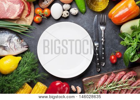Empty plate surrounded by vegetables, fish, meat and ingredients cooking. Tomatoes, eggplants, corn, beef, eggs. Top view with copy space on stone table