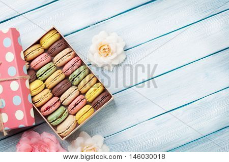Colorful macaroons and rose flowers on wooden table. Sweet macarons in gift box. Top view with copy space for your text