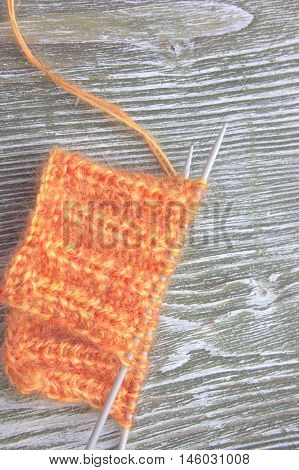 Knitting orange mohair wool ball and knitting needles on the old wooden rustic background. The beginning on knit cloth