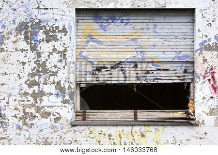 Grunge window with broken roller blinds in ghost town Doel in Belgium