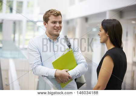 Adult student and teacher talking in university foyer