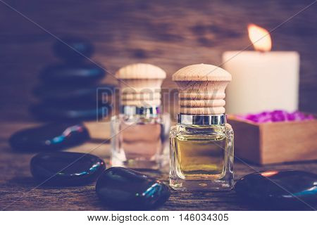 bottle of aroma essential oil or spa and natural fragrance oil with flower on wooden table Composition of spa treatment on table colorful background.