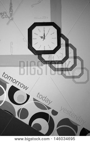 Yesterday today tomorrow sign in a conceptual black and white image. Conceptual image of clock on the wall which symbolizes life.Image show how quickly time is passing.Many transparent clocks.Below a picture of black and white circles and dark triangle.
